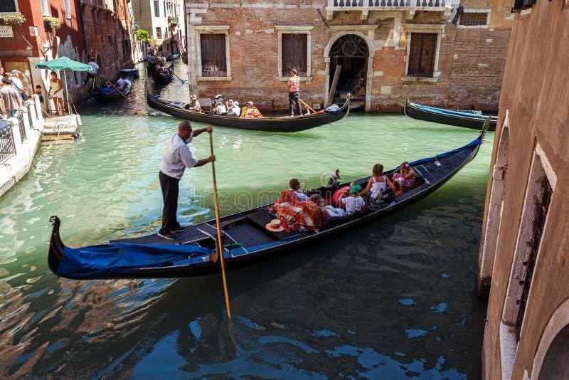 ITALIEN VENEDIG - JULI 2012: Tung trafik av gondoler med turister som kryssar omkring en liten kanal på Juli 16, 2012 i Venedig. G arkivfoton