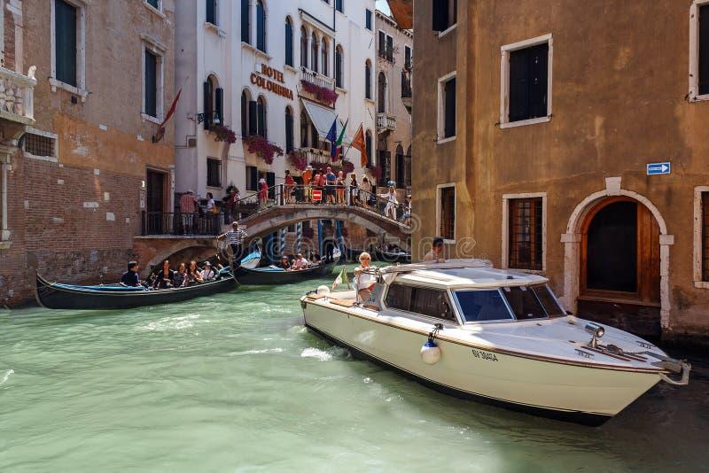 ITALIEN VENEDIG - JULI 2012: Tung trafik av gondoler med turister som kryssar omkring en liten kanal på Juli 16, 2012 i Venedig. G arkivbilder