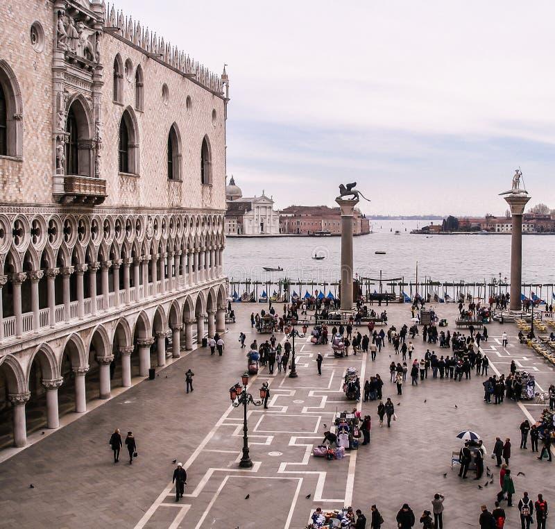 Italien Venedig, St-fläckar kvadrerar, i vinter, folk i vinterkläder som ser till Grand Canal med dogeslotten på vänstersida royaltyfri foto