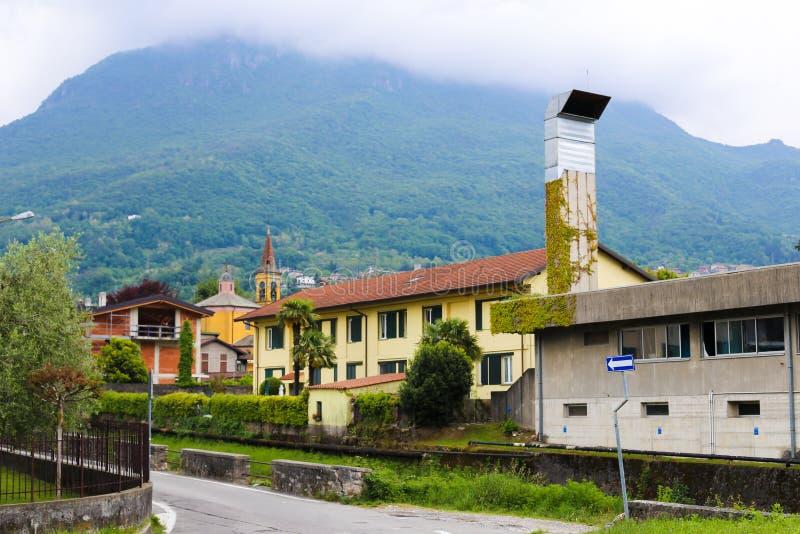 Italienare MAndello del Lario hus med fjällängberg i bakgrund arkivfoto