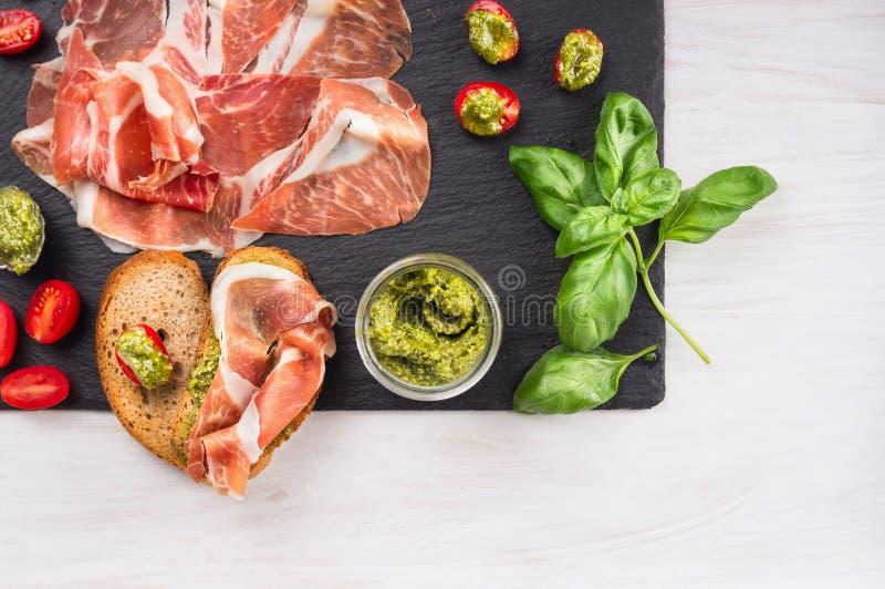 ItalienerParmaschinken mit Basilikumpesto, -tomaten und -brot lizenzfreie stockbilder
