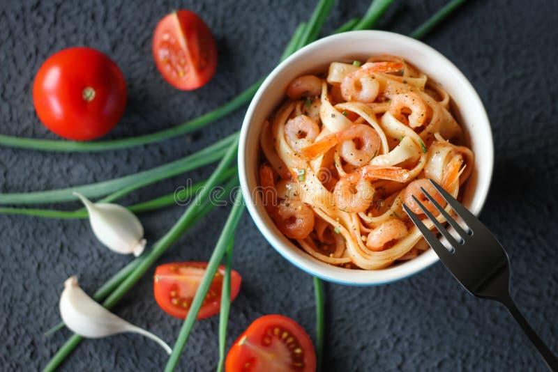 Italienische Bandnudelnteigwaren mit Garnelen und Tomatensauce auf dunklem Hintergrund lizenzfreies stockbild