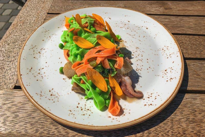 Italienische farbige Nudeln mit Meeresfrüchten - Kammmuschelgarnelen- und -krakententakeln Verziert mit den gelben Gänseblümchenb lizenzfreies stockfoto