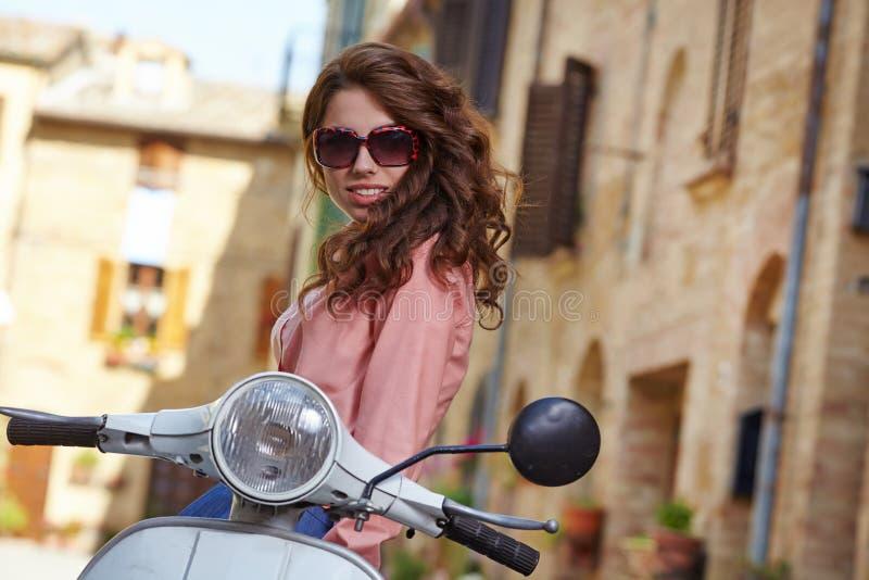 Italienische Frau, die auf einem Weinleseroller sitzt lizenzfreies stockfoto