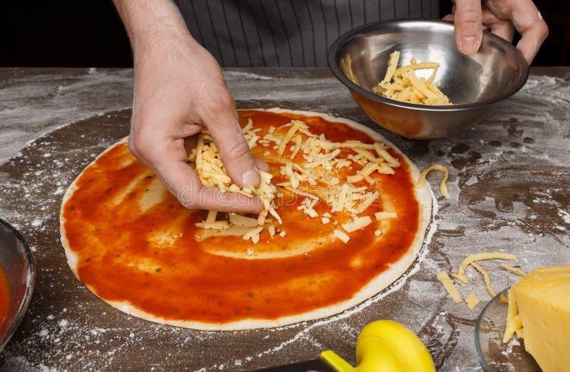 Italienische Küche Kochen Sie das Hinzufügen des geriebenen Käses Pizza lizenzfreie stockfotografie