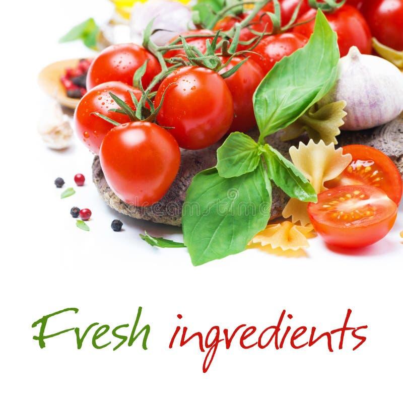 Italienische Lebensmittelinhaltsstoffe - frische Kirschtomate, -basilikum und -teigwaren stockfotos