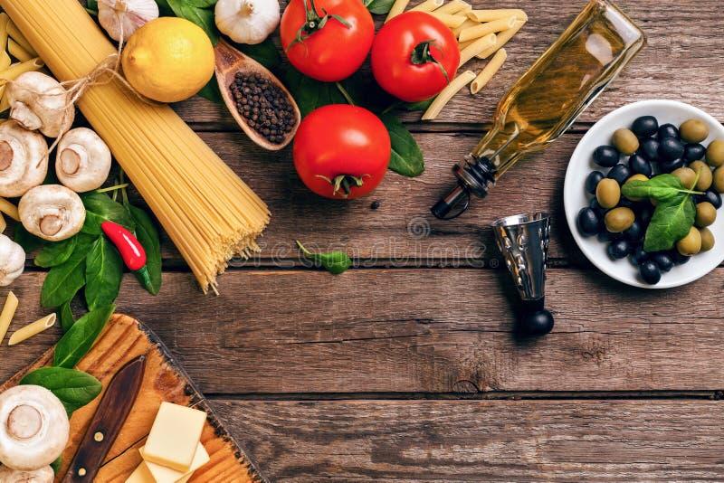 Italienische Lebensmittelkochentomaten, Basilikum, Teigwaren, Olivenöl und Käse auf hölzernem Hintergrund, Draufsicht, Kopienraum stockbild