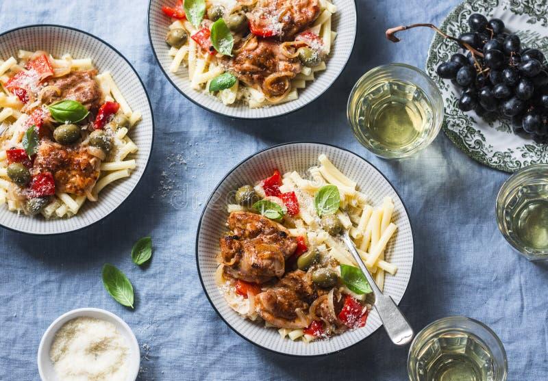 Italienische Lebensmitteltabelle Teigwaren mit langsamem Kocherhuhn mit Oliven und Gemüsepaprikas, Weißwein Auf einem blauen Hint stockfoto