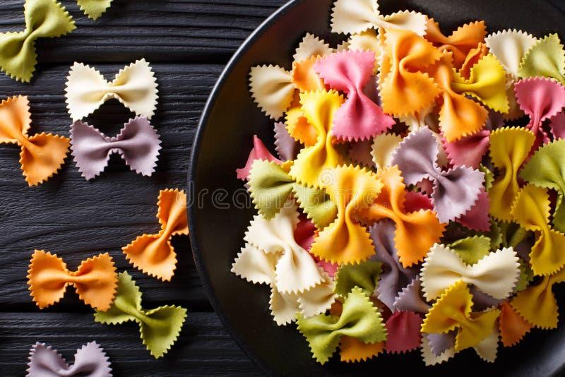 Italienische natürliche farbige farfalle Teigwarennahaufnahme auf einer schwarzen Tabelle lizenzfreie stockfotos