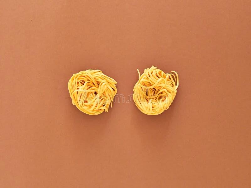 Italienische Nudelteigwaren ungekocht über braunem Hintergrund im Studio von der Draufsicht stockfotos
