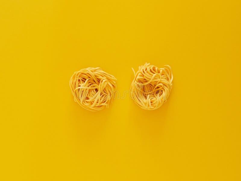 Italienische Nudelteigwaren ungekocht über gelbem Hintergrund im Studio von der Draufsicht stockfotos