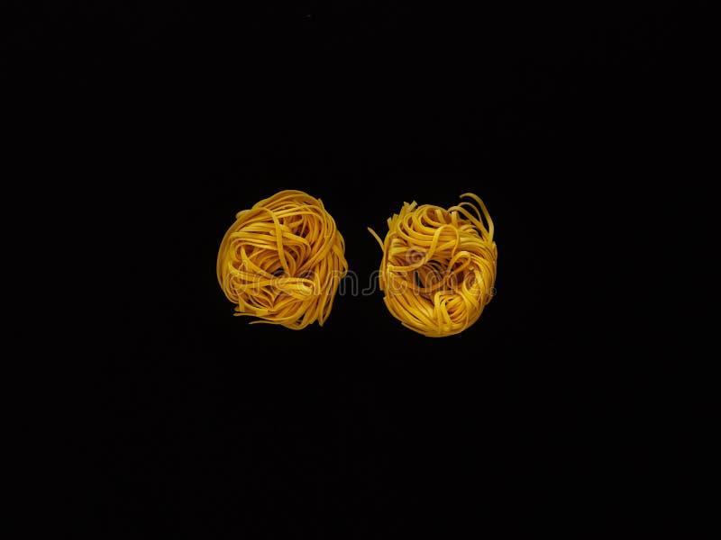 Italienische Nudelteigwaren ungekocht über schwarzem Hintergrund im Studio von der Draufsicht lizenzfreies stockfoto