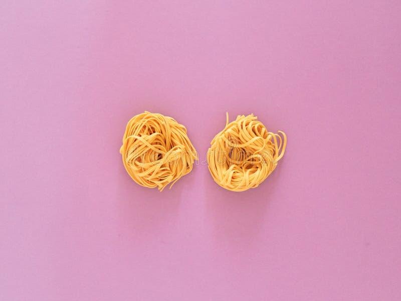 Italienische Nudelteigwaren ungekocht über violettem Hintergrund im Studio von der Draufsicht lizenzfreies stockfoto