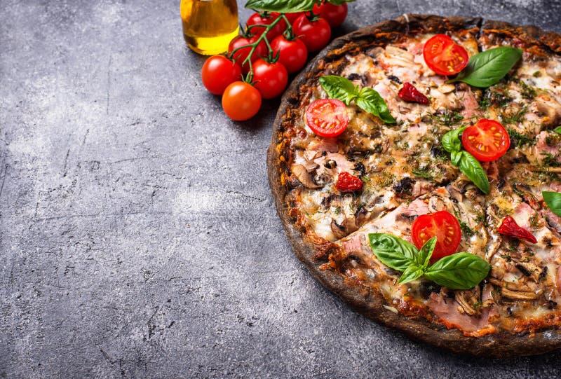 Italienische Pizza auf schwarzem Teig Modisches Lebensmittel lizenzfreies stockfoto