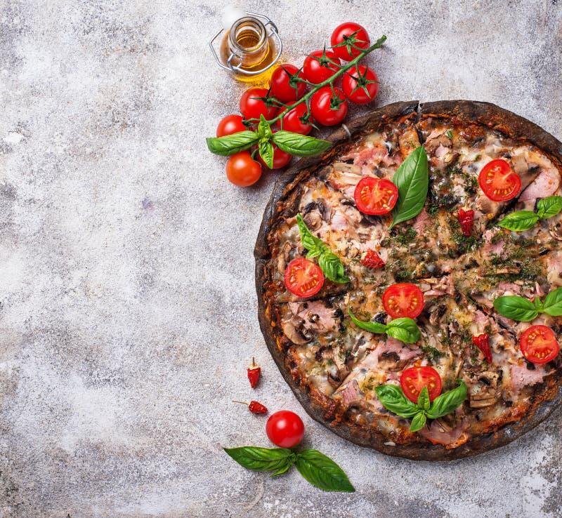 Italienische Pizza auf schwarzem Teig Modisches Lebensmittel lizenzfreie stockbilder