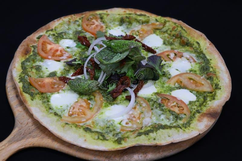 Italienische Pizza der dünnen Kruste mit Basilikum Pestosoße lizenzfreie stockfotos