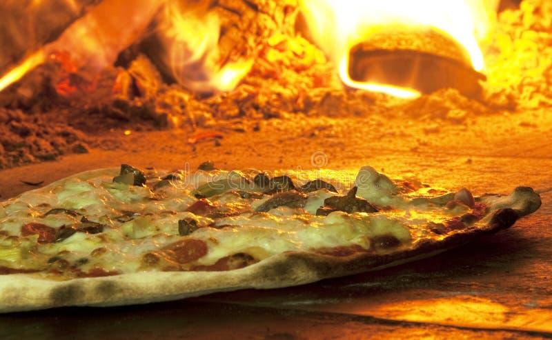 Italienische Pizza in einem hölzernen brennenden Ofen stockbild