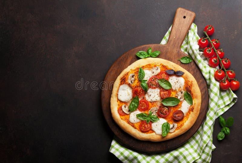 Italienische Pizza mit Tomaten, Mozzarella und Basilikum lizenzfreie stockfotos