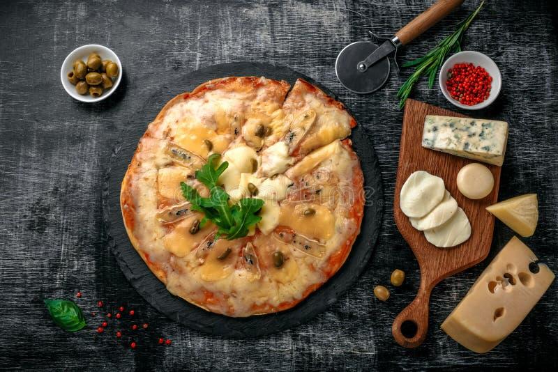 Italienische Pizza mit unterschiedlicher Art des Käses auf einem Stein und einem schwarzen verkratzten Kreidebrett Italienische t lizenzfreie stockbilder