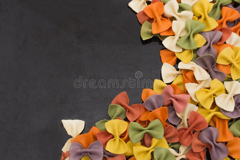 Italienische rohe mehrfarbige farfalle Teigwarennahaufnahme auf schwarzem Hintergrund mit Kopienraum stockfotografie