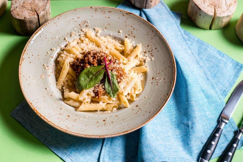 Italienische Spaghettis auf rustikalem Holztisch Mittelmeerküche mit Teigwarenbestandteilen Soße von Bolognese, Olivenöl, Basilik lizenzfreies stockbild