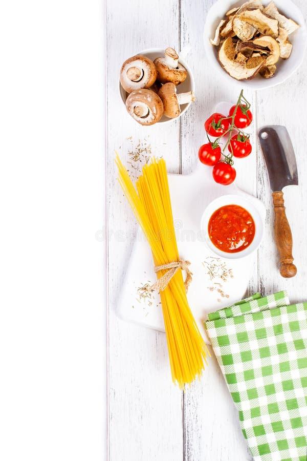 Italienische Spaghettis, Champignon, trockene Pilze, Tomatensauce, frische Kirschtomaten und Gewürze auf einem hölzernen Hintergr lizenzfreie stockfotos