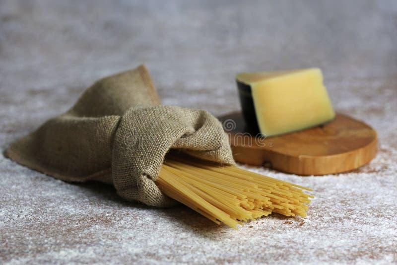 Italienische Teigwaren in der Segeltuch-Tasche mit Parmesankäse-Parmesankäse stockbild