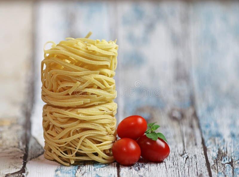 Italienische Teigwaren Fettuccine-Nester auf einem rustikalen hölzernen Hintergrund lizenzfreie stockfotos