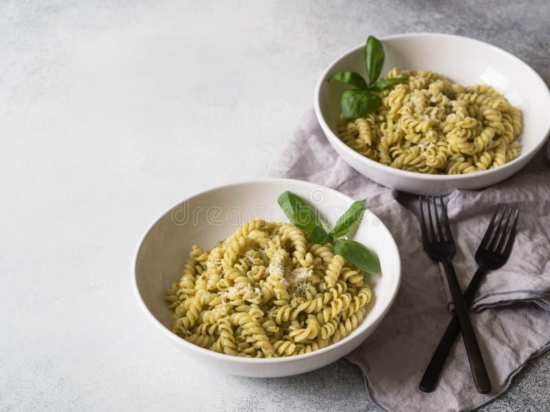 Italienische Teigwaren mit Pestosoße, frischem Basilikum und Parmesankäse in einem Weiß rollen auf grauem Hintergrund Werden Raum stockfoto