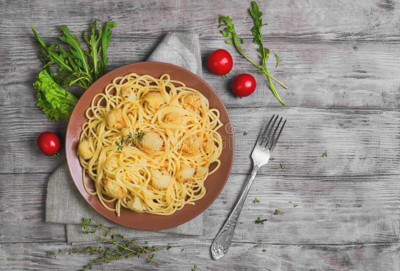 Italienische Teigwarenspaghettis auf brauner Platte mit Blumenkohl stockbild