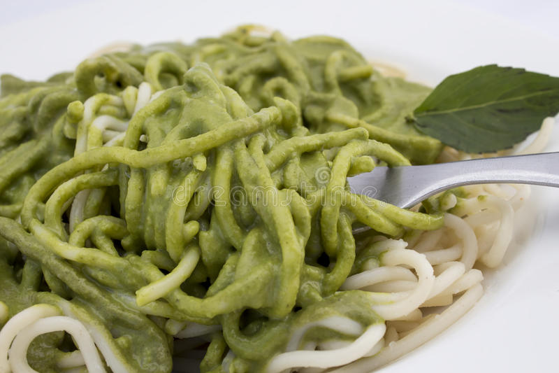 Italienische Teigwarenspaghettis mit pesto Soße- und Basilikumblattnahaufnahme lizenzfreie stockfotos