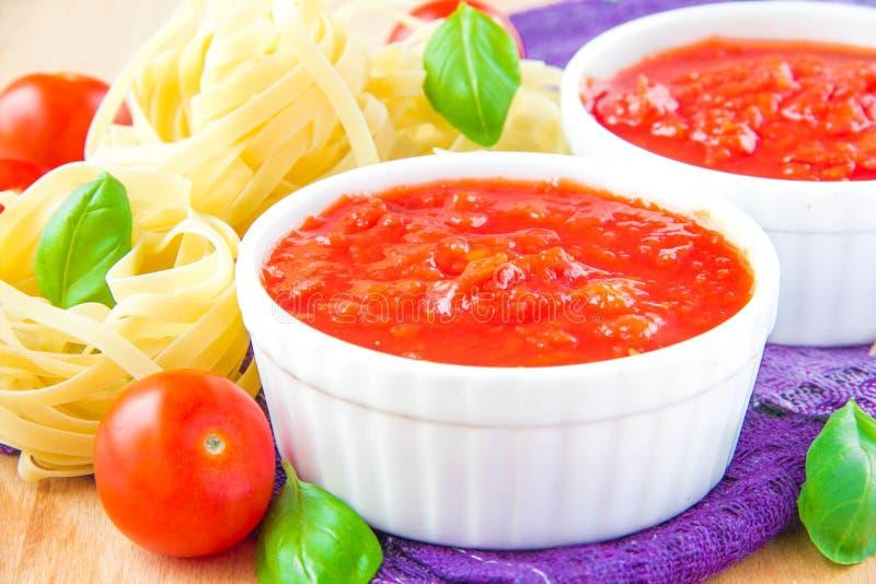 Italienische Tomatensauce in einer weißen Schale mit rohen Teigwaren, Basilikum und ch lizenzfreie stockbilder