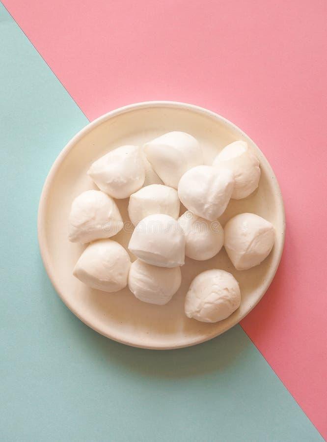 Italienischer Mozzarellakäse in der Schüssel auf dem blau-rosa Hintergrund stockfotografie