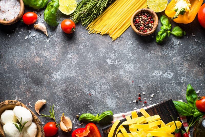 Italienischer Nahrungsmittelhintergrund Teigwaren, Kräuter, Gemüse auf schwarze Oberseite V stockbild