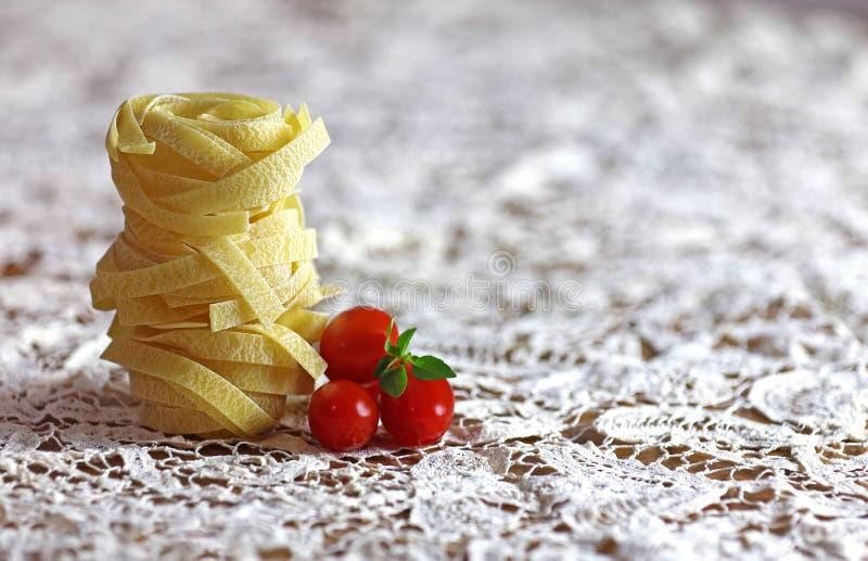 Italienischer Teigwaren Fettuccine auf einer Spitze-Tischdecke lizenzfreie stockfotografie