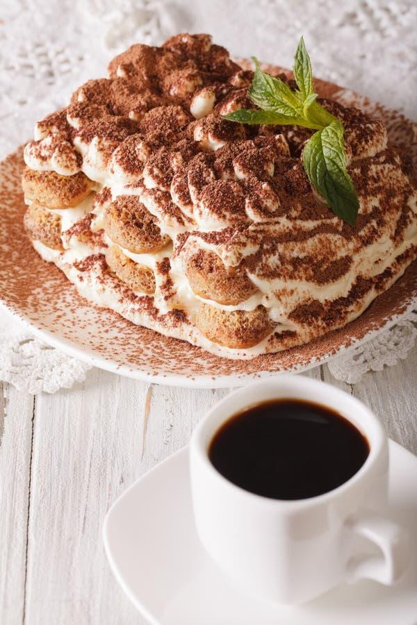 Italienischer Tiramisukuchen auf einer Platte und einer Schale Abschluss-u des schwarzen Kaffees lizenzfreie stockfotos