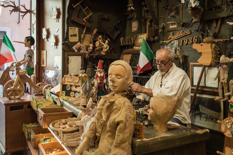 Italienischer Tischler, der an hölzernen Spielwaren Pinocchio in seiner Werkstatt/in Speicher arbeitet stockfotografie