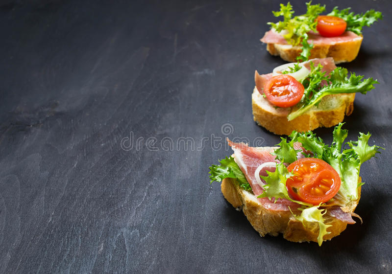 Italienisches Antipasti crostini mit Schinken, Salat und Tomate lizenzfreie stockfotografie