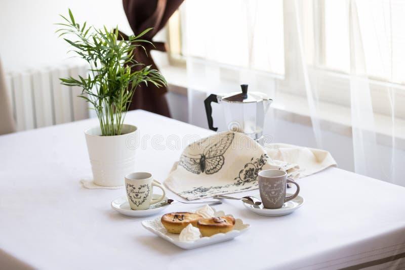 Italienisches Frühstück für Zweipersonen: Kaffee, Hörnchen, pasticiotto leccese auf dem Tisch, weißer Hintergrund in der Küche lizenzfreie stockfotografie