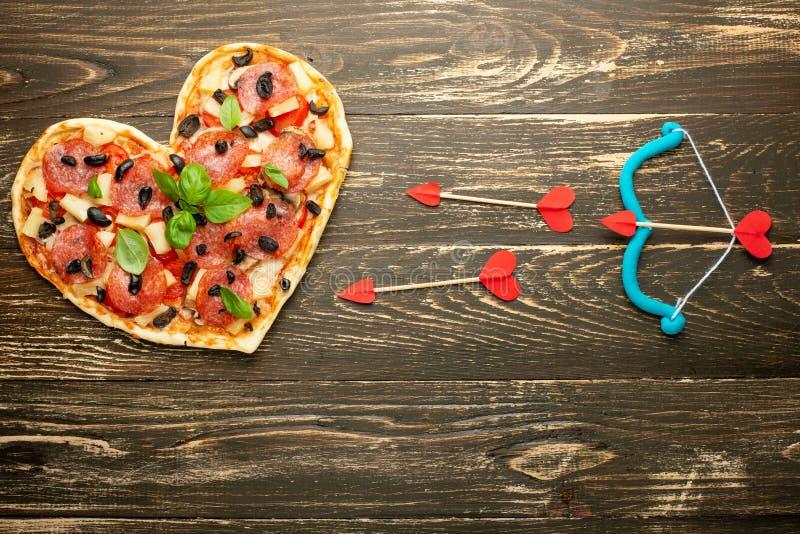 Italienisches Gebäck des Herzpizzaliebeskonzept Valentinsgrußtagesromantischen Abendessens mit Amorzwiebeln Auf einer hölzernen T stockfoto