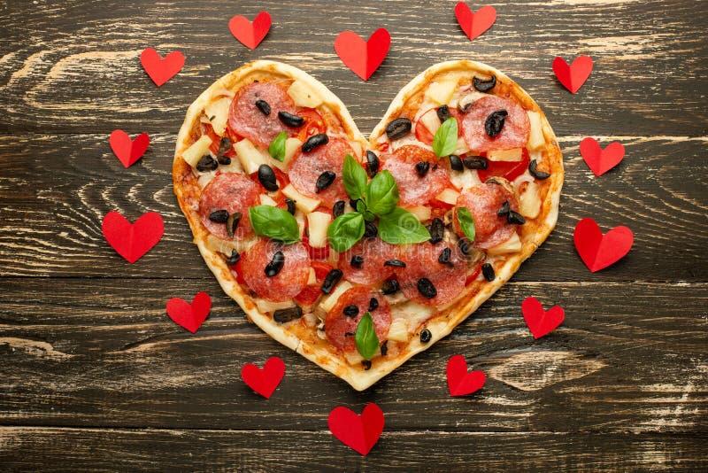 Italienisches Gebäck des Herzpizzaliebeskonzept Valentinsgrußtagesromantischen Abendessens mit roten Herzen Auf einer hölzernen T stockfotografie