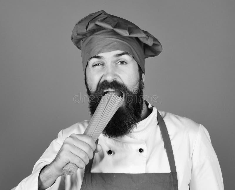 Italienisches Küchekonzept Mann oder Hippie mit Bart hält Makkaroni auf blauem Hintergrund Chef mit Bündel Spaghettis koch lizenzfreie stockfotografie