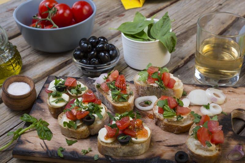 Italienisches Lebensmittel, bruschettes, Tomaten, Basilikum, Schneidebrett, köstlicher Snack, Aperitif wine, Snack, crostini, fri stockbilder