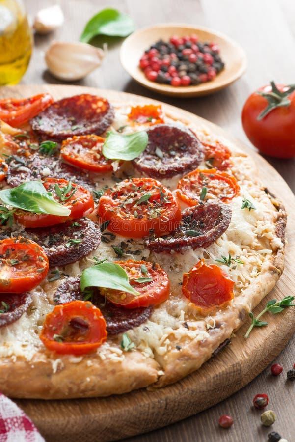 Italienisches Lebensmittel - Pizza mit Salami und Tomaten an Bord, vertikal stockbild
