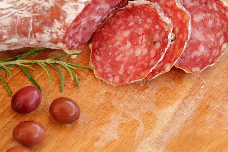 Italienisches Lebensmittel - Salami, Rosmarin, Oliven lizenzfreie stockfotos