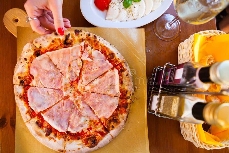 Italienisches Lebensmittelabendessen Frau, die Pizza mit Tomate Prosciutto m isst lizenzfreies stockfoto