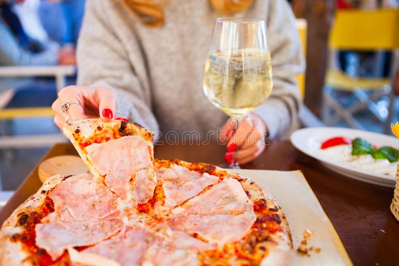 Italienisches Lebensmittelabendessen Frau, die Pizza mit Tomate Prosciutto m isst stockfotos