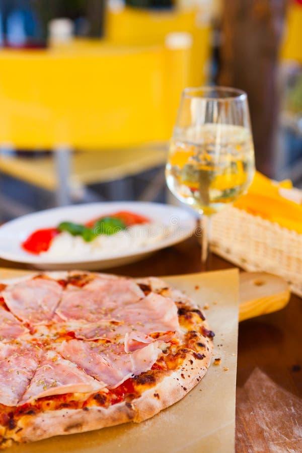 Italienisches Lebensmittelabendessen Pizza mit Tomate Prosciutto-Mozzarella gla lizenzfreie stockfotografie