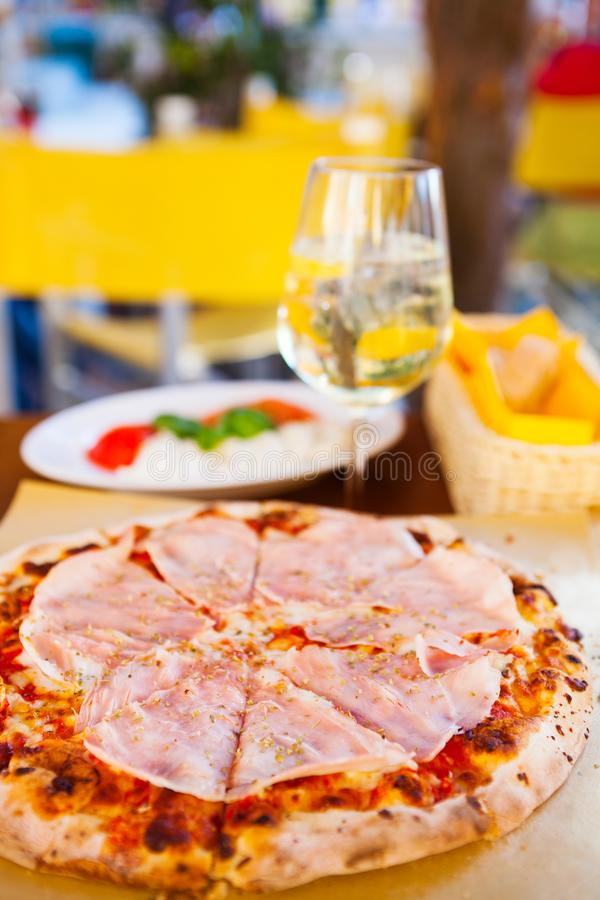 Italienisches Lebensmittelabendessen Pizza mit Tomate Prosciutto-Mozzarella gla lizenzfreie stockbilder
