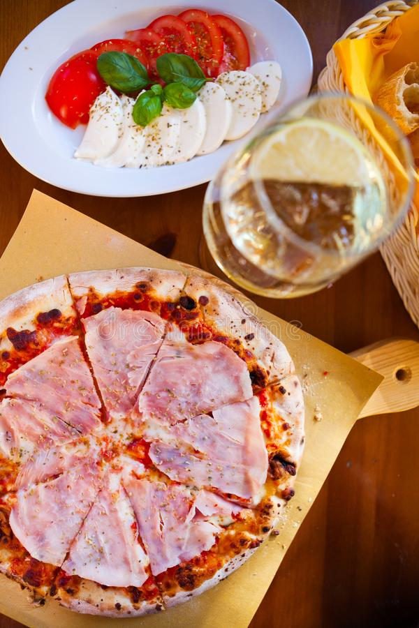 Italienisches Lebensmittelabendessen Pizza mit Tomate Prosciutto-Mozzarella gla lizenzfreies stockbild